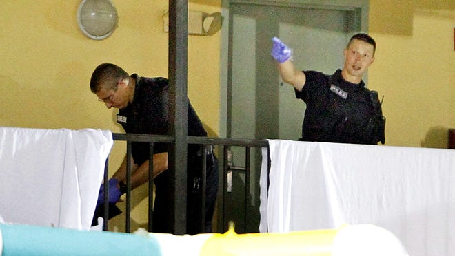 Myrtle Beach Police investigate near two bodies located behind the sheets on a walkway in front of the Bermuda Sands Resort late Saturday.