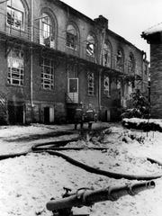 Firefighters inspect the outside walls at Holy Rosary School after a fire in the early 1980s destroyed the facility.