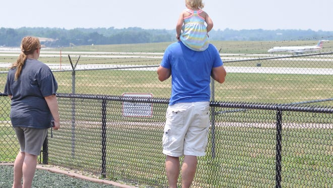 Keela Milner, left, and Patrick Riley bring their daughter Oaklyn to watch the airplanes at the Airplane Viewing Area off Donaldson Road. The family travels from Cynthiana to the airport every couple of months, because Oaklyn and Milner are always intrigued by airplanes.