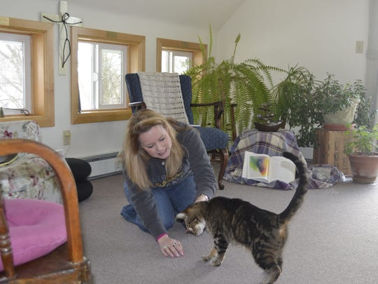 Facility coordinator Holly Hoffman plays with Fearless the cat in the upper-level chapel at The Bridge-Between Retreat Center in the Town of Morrison.