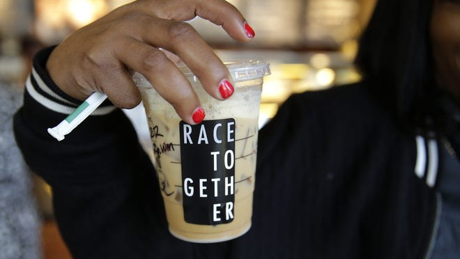 """Larenda Myres holds an iced coffee drink with a """"Race Together"""" sticker on it at a Starbucks store in Seattle. Starbucks baristas will no longer write """"Race Together"""" on customers' cups starting Sunday, ending as planned a visible component of the company's diversity and racial inequality campaign that had sparked widespread criticism in the week since it took effect."""