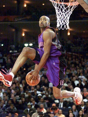 Toronto's Vince Carter passes the ball between his legs as he hangs in the air during the NBA Slam Dunk Contest.