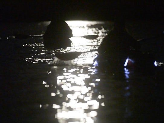 Kayaks drift through the moonlight on the Winooski