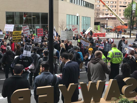 Protesters march outside the Kimpton Sawyer Hotel on