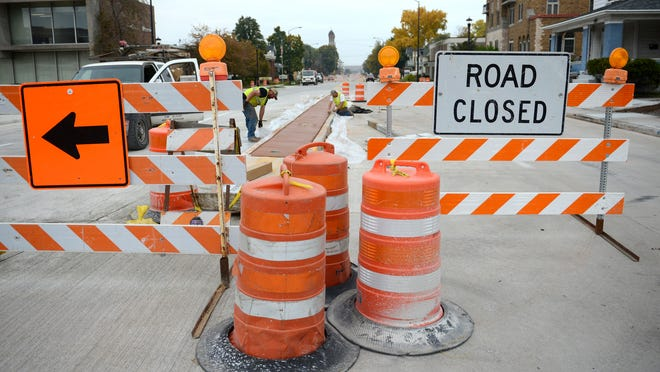 Workers from Martell Construction put finishing touches on concrete work along South Monroe Avenue on Monday.