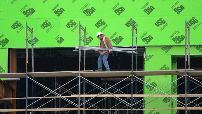 Workers set up scaffolding Jan. 19 during construction at the KI Convention Center expansion project in downtown Green Bay.
