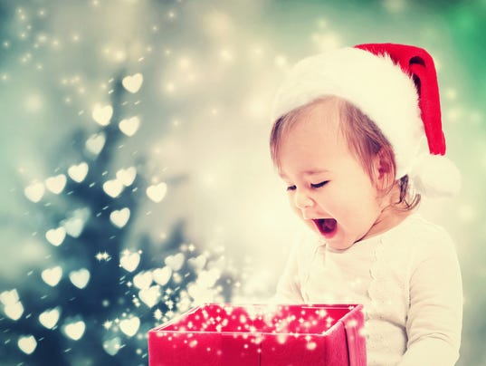 Happy Toddler girl looking at Christmas present box