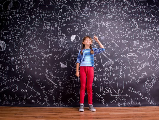 Girl with two braids, big blackboard with mathematical symbols