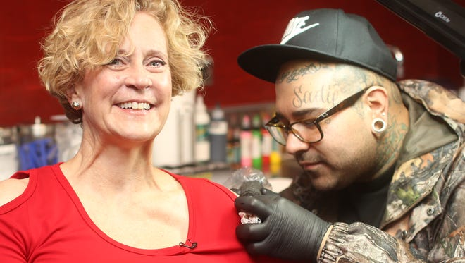 Denny Marie Post, CEO of the Red Robin chain, gets her tattoo