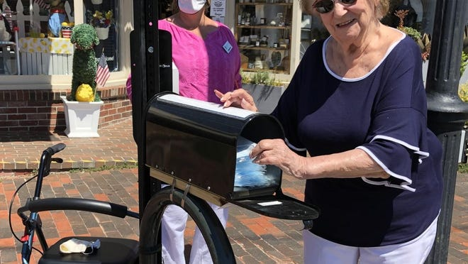 A local resident takes a free face mask from one of the four new sanitation stations located throughout Dock Square in Kennebunkport as a way to better ensure health and safety during the COVID-19 pandemic.