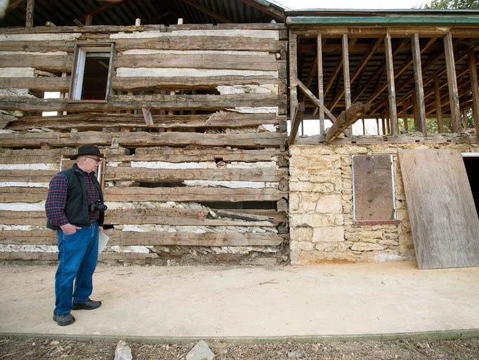 Bob Lehman with the original log home at left and the
