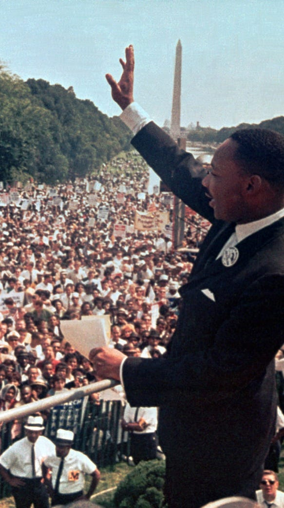 The Rev. Martin Luther King Jr. waves to the crowd