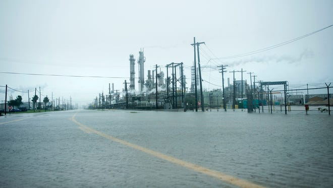 A view of the Marathon Texas City Refinery as rain from Hurricane Harvey floods a road on August 26, 2017 in Texas City, Texas. Hurricane Harvey slammed into the Texas coast late Friday, unleashing torrents of rain and packing powerful winds, the first major storm to hit the US mainland in 12 years.