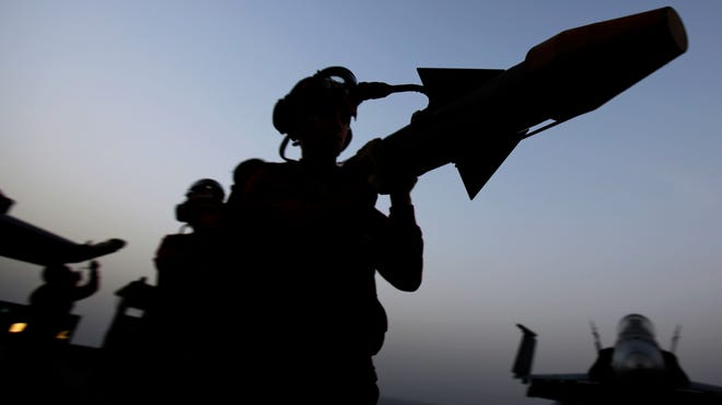 Sailors carry a missile at sunset on the flight deck of the aircraft carrier USS George H.W. Bush on Sunday, Aug. 10, 2014, in the Persian Gulf.