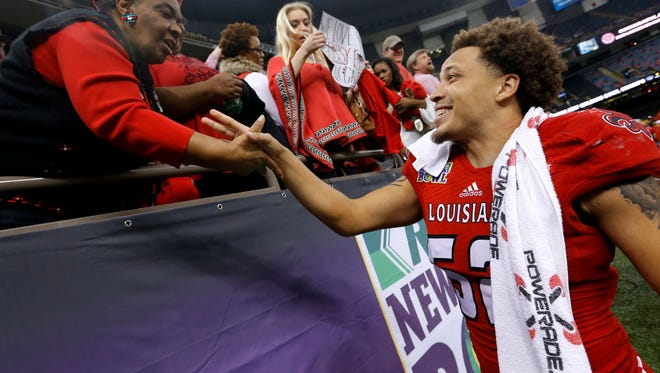 Louisiana Lafayette defensive end Dominique Tovell, right, celebrates with fans after the New Orleans Bowl on Dec. 20, 2014.
