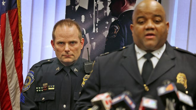 Detective Sgt. William Carter (left), listens to Indianapolis Metropolitan Police Chief Richard Hite right, during a news conference Friday to discuss the investigation into the slaying of Carmen Van Huss. Hite said Carter will continue to help with the case.
