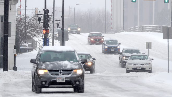 Traffic moves along Walnut St. during a snow storm on Wednesday, December 13, 2017 in Green Bay, Wis.Adam Wesley/USA TODAY NETWORK-Wisconsin