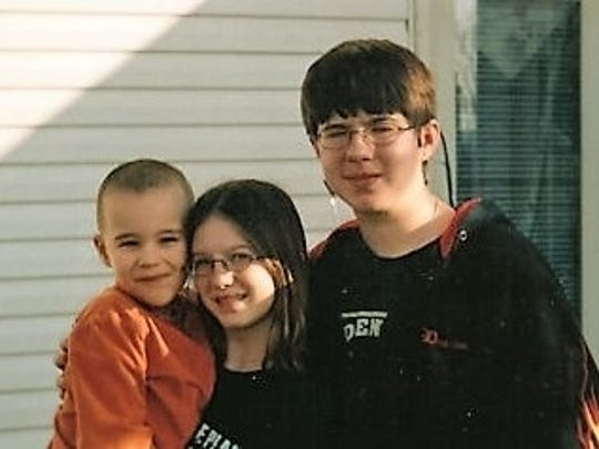 Ben Liske, 4, and brother Dylan White, 15, pose with their sister in their backyard in Nashville in 2005.