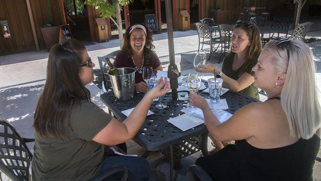 Amy De Bruyn, left, Pam Van Zwduwenburg, Sara Russell and Heather Bergman enjoy some wine and food at Oak Farm Vineyards in Lodi, which reopened to restrictive rules by the state, including sale of wine by the bottle and the purchase of food.