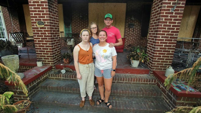 Faith and William Hunt stand outside their damaged home with daughters Grace, left, and Cana in July. The Hunt home, located on Thompson Street in Shelby, was one of three fires believed to be arson.