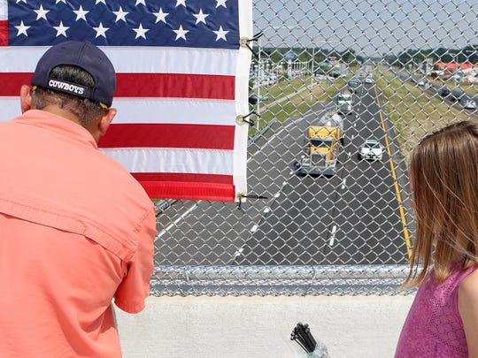Eli Valenzuela, founder and chairman of First State Manufacturing in Milford, works with his 10-year-old granddaughter, Mia Littlejohn, to place a flag on the Thompsonville Road overpass that overlooks Del. 1.