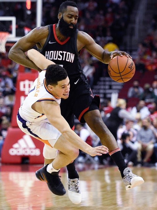 Houston Rockets guard James Harden, right, collides with Phoenix Suns guard Devin Booker during the first half of an NBA basketball game, Sunday, Jan. 28, 2018, in Houston. (AP Photo/Eric Christian Smith)