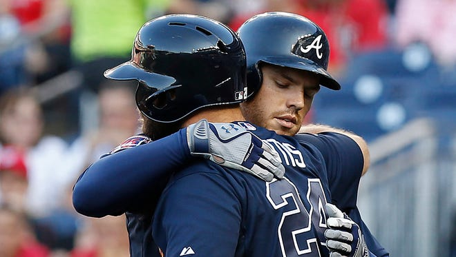 Atlanta Braves first baseman Freddie Freeman (5) celebrates with Atlanta Braves catcher Evan Gattis (24) after hitting a home run against the Washington Nationals in the top of the first inning at Nationals Park.