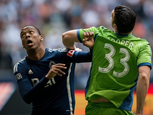 Vancouver Whitecaps' Carlyle Mitchell, left, vies for position with Seattle Sounders' Kenny Cooper during the first half of an MLS soccer game in Vancouver, British Columbia, on Saturday, July 5, 2014. (AP Photo/The Canadian Press, Darryl Dyck)
