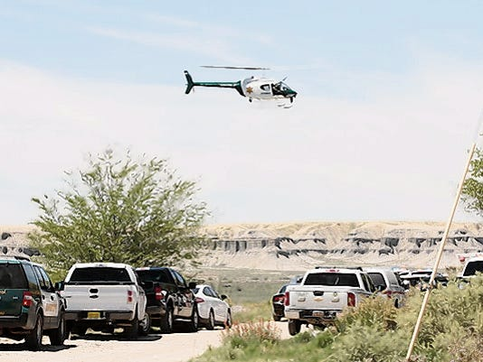 A San Juan County Sheriff's Office helicopter hovers Monday near the scene of a fatal shooting off Bluff Road in Shiprock.