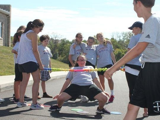 Students do the limbo at the St. Timothy School Walk-a-Thon.