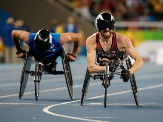In this photo released by IOC, Canada's Brent Lakatos crosses the finish line to win the gold in the men's final 100-meter T53 athletics event at Olympic Stadium during the Paralympic Games in Rio de Janeiro, Brazil, Friday, Sept. 9, 2016.
