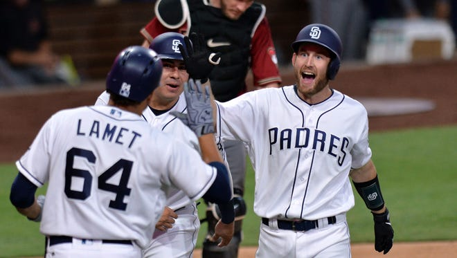 Sep 20, 2017; San Diego, CA, USA; San Diego Padres catcher Rocky Gale (right) is congratulated by starting pitcher Dinelson Lamet (64) and followed by third baseman Christian Villanueva (middle) after hitting a two run home run to tie the game during the second inning against the Arizona Diamondbacks at Petco Park. It was the first Major League home run for Gale. Mandatory Credit: Jake Roth-USA TODAY Sports
