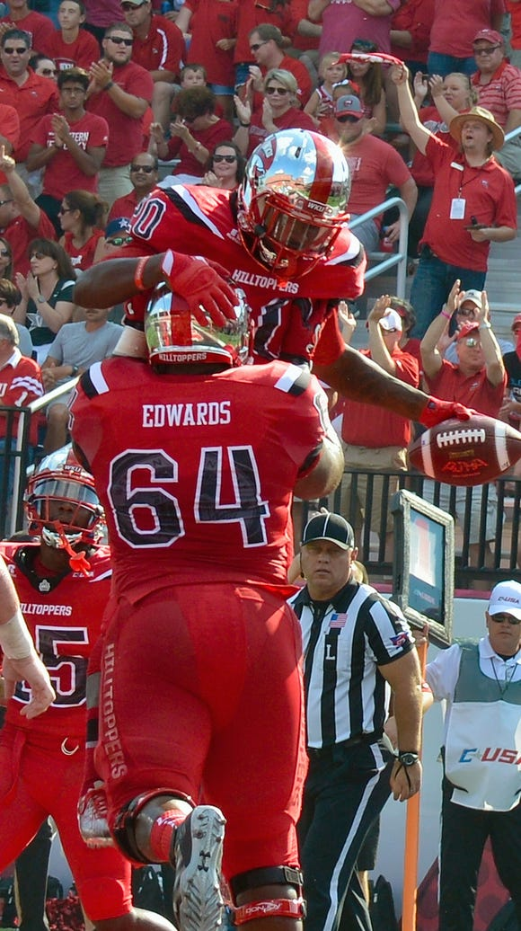 Western Kentucky offensive lineman Dennis Edwards holds up running back Anthony Wales (20) during a 2016 game.