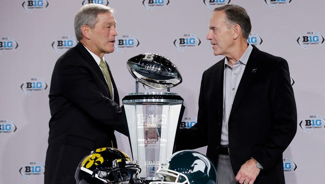 Iowa head coach Kirk Ferentz, left, and Michigan State head coach Mark Dantonio shake hands during a news conference for the Big Ten Conference championship NCAA college football game Friday, Dec. 4, 2015, in Indianapolis.