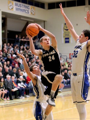 Luke Cooper of Covington goes up against Spencer Sproul of Carroll for two of his 16 points in the sectional championship game.