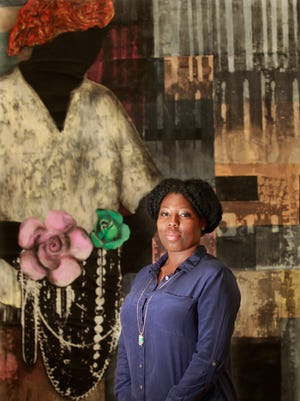 """Tyanna Buie is photographed in front of her artwork """"Incarnation,"""" a memorial to her grandmother that she never knew and her late uncle who died anonymously in prison."""