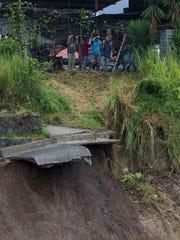 Workers observe a landslide on the outskirt San Jose,