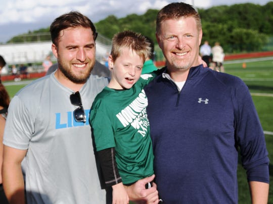 South Lyon's Tyler Glaszek (middle), 7, poses for a photo at the Novi Fantasy Football Camp with Lions punter Sam Martin (left) and father Tom Glaszek.