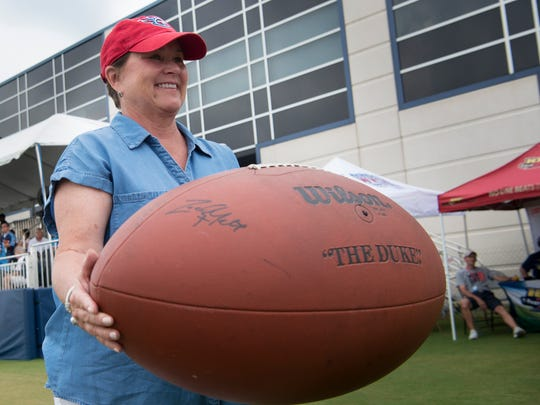 Titans controlling owner Amy Adams Strunk holds a fan's giant football as she watches training camp practice at Saint Thomas Sports Park Tuesday, Aug. 1, 2017 in Nashville, Tenn.