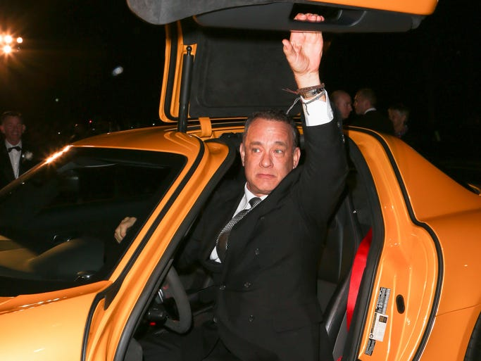 Actor Tom Hanks reaches up to the door of a Mercedes-Benz at the Palm Springs International Film Festival Awards Gala