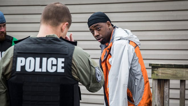 Police apprehend Shawn English, wanted for allegedly dealing heroin, at a residence near Second and Elliot Streets Wednesday morning. The arrest was part of a joint operation between county and city police targeting more than two dozen drug dealers.