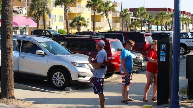 Beachgoers use a parking kiosk near the Tybee Island pier on July 4, when some 12,300 carloads of visitors filled the town.