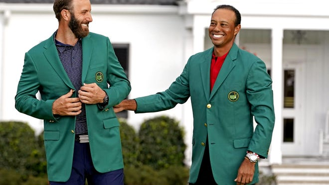 2019 Masters champion Tiger Woods presents Dustin Johnson with the green jacket forafter winning the Masters Tournament on Sunday at Augusta National.