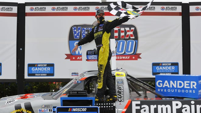 Grant Enfinger, driver of the No. 98 Ford, celebrates in Victory Lane after winning the NASCAR Gander Outdoors Truck Series Vet Tix Camping World 200 at Atlanta Motor Speedway on Saturday in Hampton, Georgia.