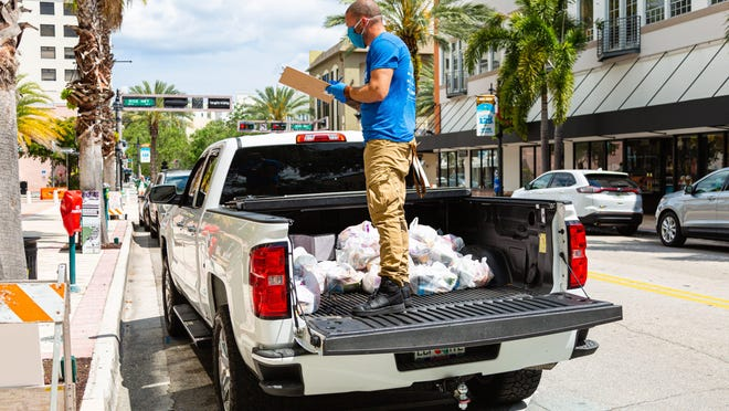 Joey Nieves stands in the bed of a pickup with the bags of food The Lord's Place is giving out at the Mandel Public Libraryin downtown West Palm Beach, on Tuesday March 31, 2020. The Lord's Place is still delivering food two days a week during the coronavirus pandemic.