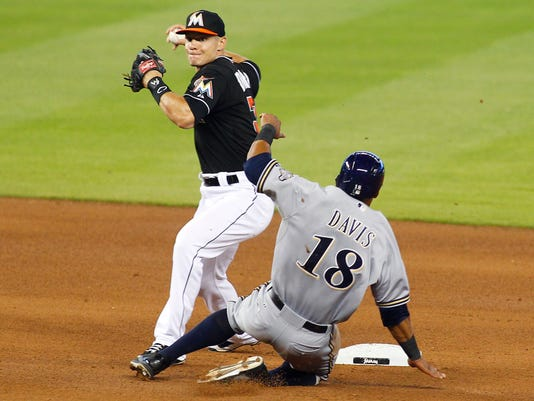 Miami Marlins second baseman Derek Dietrich, left, avoids a sliding Milwaukee Brewers' Khris Davis to turn a fifth-inning double play during a baseball game in Miami, Saturday, May 24, 2014. (AP Photo/Joe Skipper)