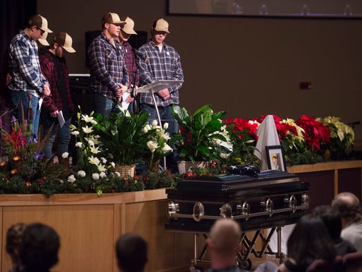 Friends of Jack Headley stand over his casket to share