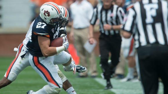 Auburn running back Chandler Cox (27) is tackled by Auburn defensive back Markell Boston (11) during the Auburn A-Day spring game on Saturday, April 18, 2015, at Jordan-Hare Stadium in Auburn, Ala.