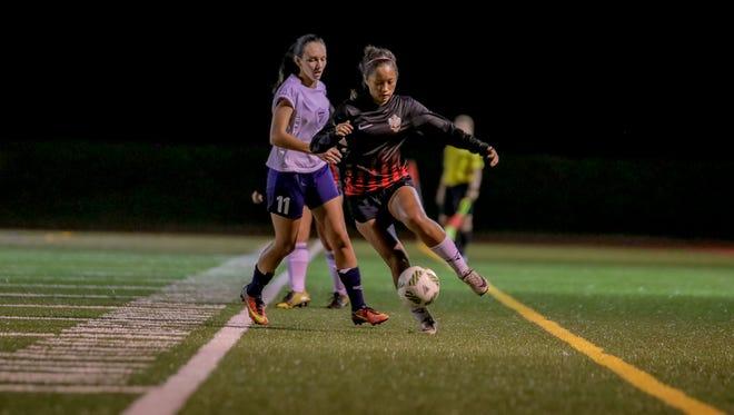 Guam High School's Logyn Lallatin and St. John's School's Jenna Han battle for ball possesion.