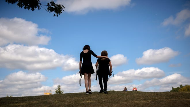 Senior Rachael Steffens, left, guides freshman Autumn Michels to the field for band practice on Monday, Sept. 18, 2017, at Laingsburg High School. The two have formed a strong friendship since meeting at band camp and being by each other's sides during band performances and practices.